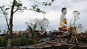 A Buddha statue remains standing at a temple destroyed by Cyclone Nargis