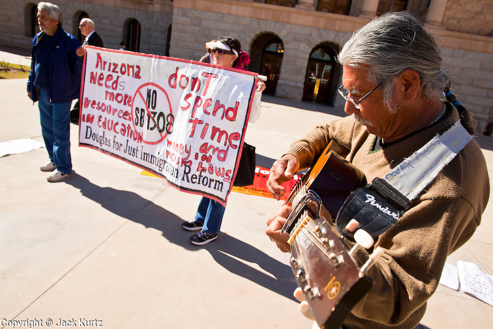 07 FEBRUARY 2011 - PHOENIX, AZ: FRANCISCO ROBLES, right, from Tucson, AZ, plays guitar while others demonstrate in support of birthright citizenship at the Arizona Capitol Monday, February 7. The Arizona State Legislature, led by the State Senate is debating the 14th Amendment, which would bar US citizenship for children born in the US to undocumented immigrants. The bill has broad support among Republicans, who are the majority party, in the state legislature but not among Democrats. The law is also very unpopular in the state's Latino and immigrant communities.        Photo by Jack Kurtz