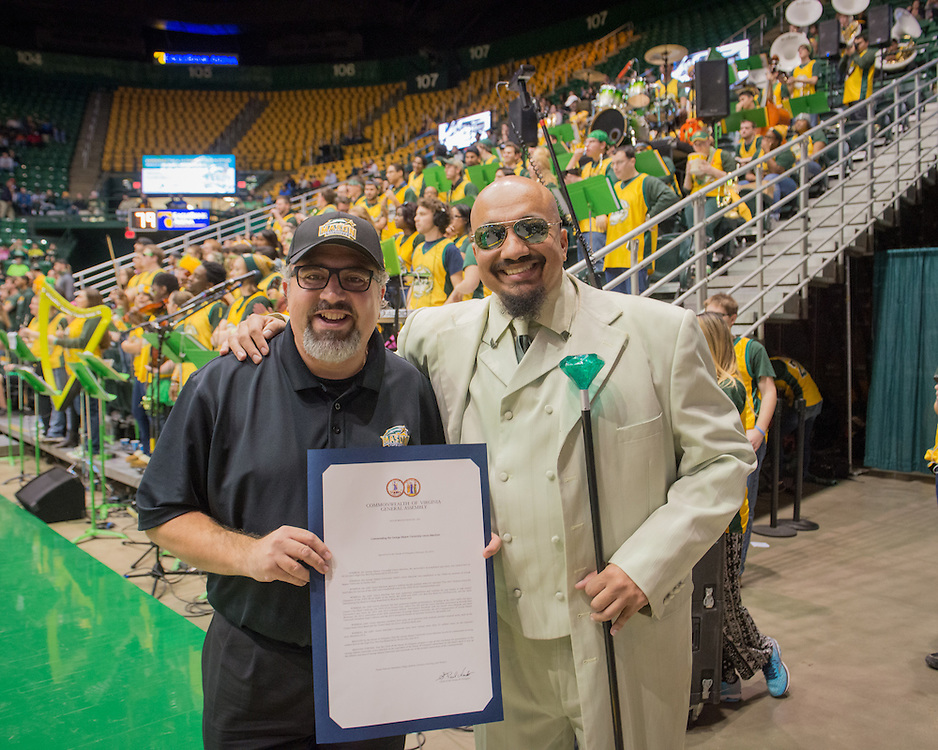 December 5, 2015 - Fairfax, VA - A day in the life of &quot;Doc Nix,&quot; aka Dr. Michael Nickens, the Director of the Athletic Bands for George Mason University. Here, Doc Nix is presented with a certificate from the VA House of Delegates with Delegate Ramadan during the game for the band's excellence.<br /> <br /> Photo by Susana Raab