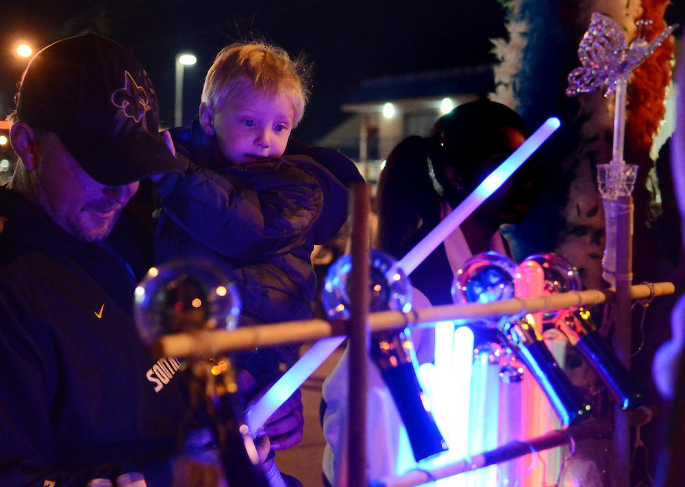 Dan Addison and his son Ayden, 2, buy a light-up-toy from a street vendor on Thursday during Hattiesburg's first Mardi Gras Parade. Bryant Hawkins/The Hattiesburg American