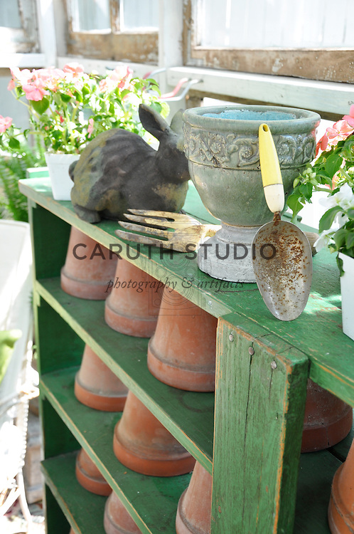 Vintage garden: Detail of terracotta pots on shelving inside glass shed