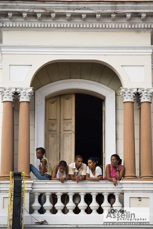 People watch from a balcony as a parade goes by during the Fire festival in Santiago, Cuba on Friday August 8, 2008.