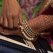 Bride wearing jewellery on a foot before the gujarati wedding.