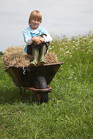 Boy (5-6) sitting on hay in wheelbarrow in field portrait