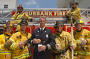 6/29/2004 Burbank California-(l-r) Top: Ron Barone, Jim Goldstein, bottom Brian Williamson, Ken Allen,(center in dress uniform) Steve Briggs, Pete Garcia and Gary McDiffett.  ....All names CQ...Briggs, a Captain at Burbank Fires Station 11, stands with members of his engine company during a photo shoot for a calendar.  Briggs won a baking contest for an old family recepie for this apricot, oatmeal cookie. Photo by John McCoy/Los Angeles Daily News
