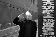 A man dressed in a space-age helmet salutes as he attempts to attract customers and sell an electronic device in Beijing, China