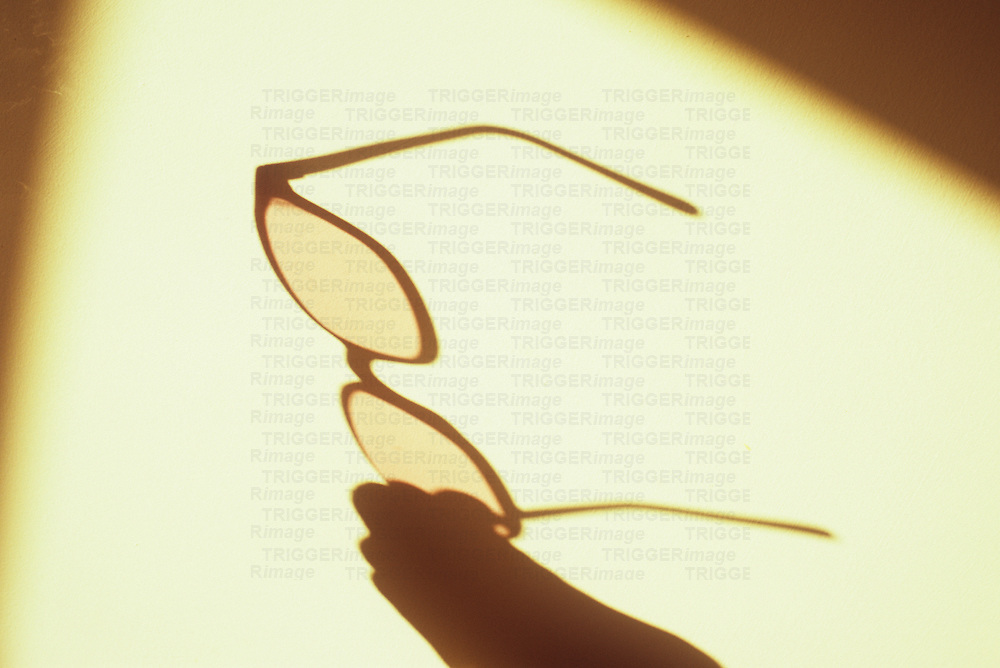 Shadow of hand holding spectacles framed within shadow of window in warm light