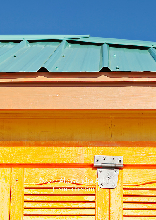 Gold-orange shutters contrast with clear blue sky on colorful building in Vicksburg, MS.