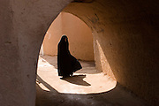 A lone woman in black chador (tent) walks along one of the labyrinth of covered streets and alleys that wind through the ancient mud brick city of Yazd, Iran.