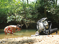 Young woman in lake drinking water backpack on shore