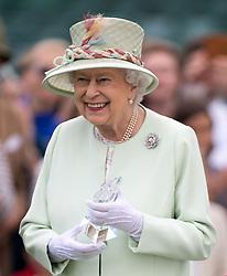 Queen Elizabeth II presents awards during the Bentley Motors Royal Windsor Cup Final at Guards Polo Club, Windsor Great Park, Egham, Berkshire.