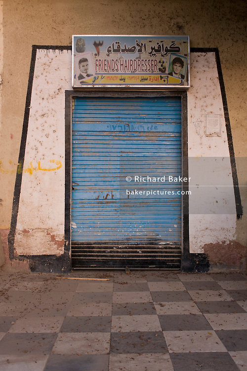 Closed shutters of a barbers business using the ancient Egyptian pylon design for its entrance, in the village of Bairat on the West Bank of Luxor, Nile Valley, Egypt.