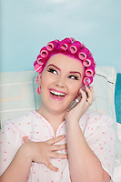 Happy young woman talking on mobile phone with hair curlers