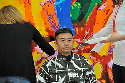 "© Licensed to London News Pictures. 13/09/2017. London, UK. Renowned Chinese artist Liu Bolin begins his new work ""The Disappearing Act"", the world's first ever live time-based performance in the context of an art fair.  Taking place during the START Art Fair at the Saatchi Gallery, Chelsea, specially chosen local artists are being directed to help Bolin disappear into the background of Lego bricks which depict a sunflower.  Photo credit : Stephen Chung/LNP"