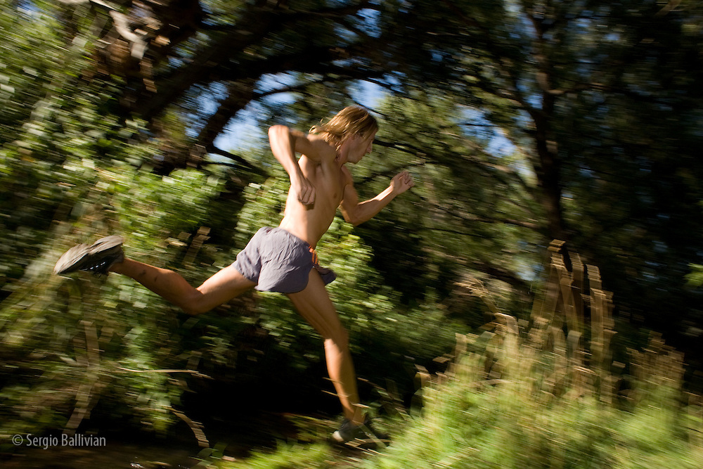 A mid-adult man running through the forest by a creek in Boulder, CO