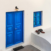 White house with blue door in greek style