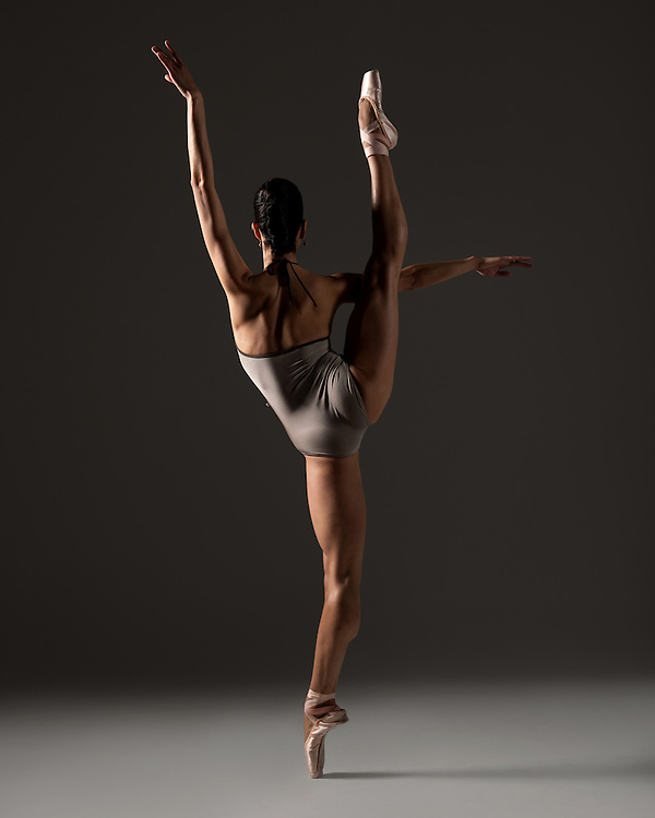 Contemporary female ballet dancer, Maria Barriga, in a la seconde, taken in the photo studio on a black background. Photograph taken in New York City by photographer Rachel Neville.