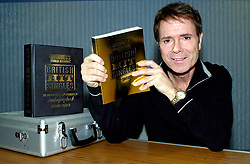 Sir Cliff Richard autographs a special edition of the Guinness book of Hit Singles back stage at the Hallam FM arena on the 8th November 2002<br />