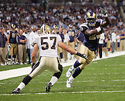 ST. LOUIS - SEPTEMBER 23:  Running back Marshall Faulk #28 of the St. Louis Rams twists his body to avoid a tackle by linebacker Colby Bockwoldt #57 of the New Orleans Saints at the Edward Jones Dome on September 23, 2005 in St. Louis, Missouri. The Rams defeated the Saints 28-17. ©Paul Anthony Spinelli *** Local Caption *** Marshall Faulk;Colby Bockwoldt
