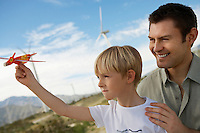 Boy (7-9) holding toy glider with father at wind farm