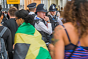 Crowds pass through police cordons (which are on the look out for potential troublemakers) as they  flock to see the 50th Notting hill carnival on Bank Holiday Monday.