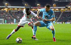MK Dons's Ousseynou Cisse (left) and Coventry City's  	Marc McNulty battle for the ball