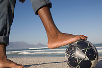 Foot on soccer ball beach scene