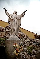 """Una statua del Cristo nel cortile di """"Vincent City"""", residenza del pittore salentino """"Vincent Brunetti""""nei pressi di Guagnano in provincia di Lecce. 29/03/2009 (PH Gabriele Spedicato) ..VINCENT BRUNETTI.Affettuosamente identificato con l'appellativo """"LA LIBELLULA DEL SUD"""", Vincent Brunetti è oggi considerato uno dei personaggi più emblematici della vita artistica meridionale..Nato a Guagnano di Lecce il 3 dicembre 1950 e residente a Milano da oltre vent'anni dove per i meriti artistici (egli è infatti pittore e scultore) gli è stato conferito nel 1970 l'AMBROGINO D'ORO. Fu colpito in tenera età dal virus della poliomelite. Gli effetti devastanti della malattia a seguito di due delicati interventi al piede sinistro lo stavano portando ad una quasi totale immobilità..Comincia comunque a dipingere e consegue, con il massimo dei voti, il diploma alla Scuola d'arte di Lecce..Dopo essere stato a Torino, si trasferisce a soli venticinque anni a Milano dove riceve numerosi riconoscimenti ed entra in contatto con elementi di spicco della scena artistica milanese come Francesco Messina (sotto la cui guida frequenta l'Accademia di Brera); Giacomo Manzù che lo segue ed incoraggia nel corso della sua attività; Arnaldo Pomodoro che lo accoglie presso la sua Bottega..Sempre a Milano, egli collabora con l'attrice Paola Borboni ed il poeta Bruno Villar alla realizzazione di numerose attività culturali e di diversi programmi televisivi..Con il passare degli anni egli è sempre più debilitato dalla malattia..Grazie alla geniale scoperta di Mariano Orrico, ideatore """"Lamina Bior"""" secondo il quale, ogni genere di malattia può essere sconfitta con il proncipio dell'elettricità statica, Vincent Brunetti ha potuto recuperare in pieno la sua vitalità e gioia di vivere..Nella sua """"DANZA"""" propiziatoria è espresso in pieno il bisogno di LIBERTA' che è nascosto nel cuore di ogni uomo e nel suo """"VOLO"""" il desiderio di liberarsi dal peso della materia..Nell'elasticità delle articolazioni rese forte"""