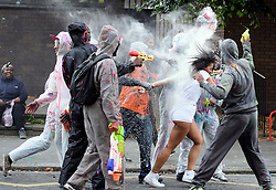 © Licensed to London News Pictures. 28/08/2016. London, UK. A woman being covered in powdered paint as revellers enjoy Jouvert, a paint fight that officially marks the start of the Notting Hill carnival. The two day event is the second largest street festival in the world after the Rio Carnival in Brazil, attracting over 1 million people to the streets of West London. Photo credit: Ben Cawthra/LNP