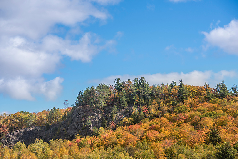 A rock outcrop is fringed by maples in fall color near Marquette, Michigan.