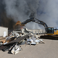 A excavator was brought to American Furniture to tear down two breezeway connecting lanes so they could create a fire break and contain the fire.