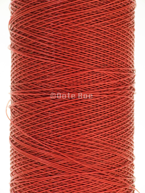 close up of spool with a red thread