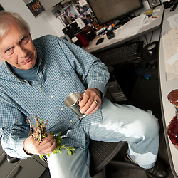 Bob Edwards, holding a mint julep cup and an upside-down bouquet of mint, demonstrating his distaste for mint juleps.