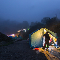 Peru, Glowing lights illuminate interior of cook tent in fog at dusk along Inca Trail to Machu Picchu