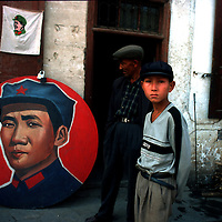 KASHGAR, 30 SEPTEMBER 2001: :an antiques dealer looks at a Mao Zedong propaganda plate which stands outside his store.  . . Uighur muslims in southern Xinjiang province lead very basic lifestyles and have an average monthly income of about 50 US$.. (photo by: katharina hesse/Grazia Neri).