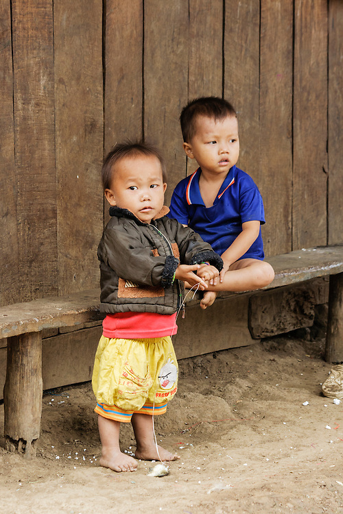 Two young Hmong boys in a village outside Luang Prabang in Laos. The Hmong people are an Asian ethnic group from the mountainous regions of China, Vietnam, Laos, and Thailand.