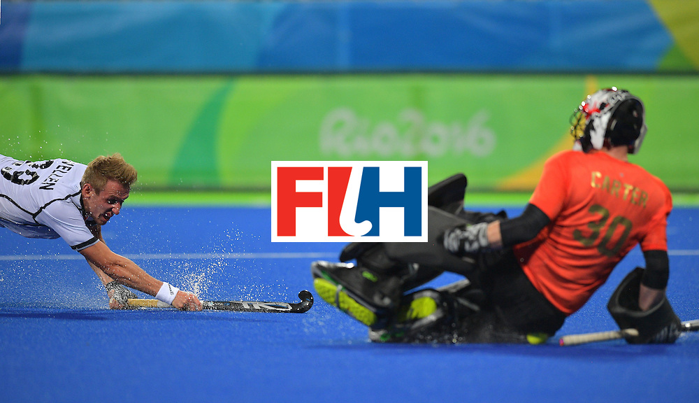 Germany's Niklas Wellen (L) dives in front of Canada's goal keeper David Carter during the men's field hockey Canada vs Germany match of the Rio 2016 Olympics Games at the Olympic Hockey Centre in Rio de Janeiro on August, 6 2016. / AFP / Carl DE SOUZA        (Photo credit should read CARL DE SOUZA/AFP/Getty Images)