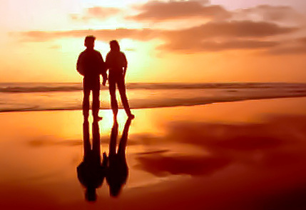 A couple is silhouetted on a wet beach at sunset in Baja California, Mexico