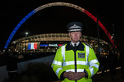 "© Licensed to London News Pictures. 17/11/2015. LONDON, UK. Metropolitan Police Commissioner, Sir Bernard Hogan-Howe, stands outside Wembley Stadium ahead of the football friendly between England and France. The stadium is illuminated with the French colours, and the words ""Liberté, Égalité, Fraternité"".  Photo credit : Stephen Chung/LNP"