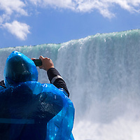 Canada, Ontario, Niagara Falls. Tourist in blue poncho photographing the Falls from the Maid of the Mist cruise.