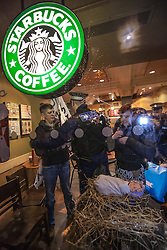 © Licensed to London News Pictures . 08/12/2012 . Manchester , UK . Protesters pushed in to the branch and set up a makeshift Christmas nativity scene in the shop window before police ejected them . UKUncut hold a demonstration against corporate tax avoidance outside a branch of Starbucks on St Ann's Square in Manchester City Centre today (8th December 2012) . Photo credit : Joel Goodman/LNP