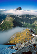 Mount Balloon (6080 feet) pierces clouds above MacKinnon Pass and the Milford Track, seen from the flanks of Mt. Hart, in Fiordland National Park, South Island, New Zealand. 15 feet of rain per year drenches the area. The Milford Track is a fun 4-day hike, starting from a boat launch on Lake Te Anau, wandering through glaciated valleys and over an alpine pass to Milford Sound, an impressive glacier-carved fiord. You can optionally stay an extra night and tour Milford Sound via a one-day kayak trip. In 1990, UNESCO honored Te Wahipounamu – South West New Zealand as a World Heritage Area.