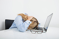 Tired businesswoman resting head on laptop in office
