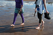 Two women walking barefoot in February throught the mud to the Stop the Bridge public rally and demonstration on the north shore of Flathead Lake organized by CANSC (Community Association for North Shore Conservation).