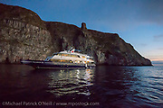 The Galapagos Sky Liveaboard dive vessel rests at night in a protected cove in Wolf Island, Galapagos Islands, Ecuador