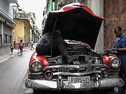 Men work to repair a vintage car. Unable to import spare parts, Cubans often pull parts from other vehicles and even create custom components of their own.