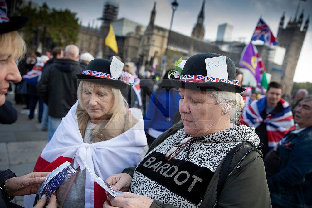 © Licensed to London News Pictures. 31/10/2019. London, UK. Pro-Brexit protesters wear bowler hats decorated with 'OUT' signs gather near Parliament on what would have been the United Kingdom's last day as a member of the European Union. The date of Brexit had been moved to January 31, 2020 after MPs failed to pass Prime Minister Boris Johnson's withdrawal agreement. Photo credit: Peter Macdiarmid/LNP