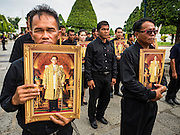 29 OCTOBER 2016 - BANGKOK, THAILAND: Men hold pictures of the late Bhumibol Adulyadej, the King of Thailand, while they walk into the Grand Palace to homage to the King. Saturday was the first day Thais could pay homage to the funeral urn of the late Bhumibol Adulyadej, King of Thailand, at Dusit Maha Prasart Throne Hall in the Grand Palace. The Palace said 10,000 people per day would be issued free tickerts to enter the Throne Hall but by late Saturday morning more than 100,000 people were in line and the palace scrapped plans to require mourners to get the free tickets. Traditionally, Thai Kings lay in state in their urns, but King Bhumibol Adulyadej is breaking with tradition. His urn reportedly contains some of his hair, but the King is in a coffin,  not in the urn. The laying in state will continue until at least January 2017 but may be extended.       PHOTO BY JACK KURTZ
