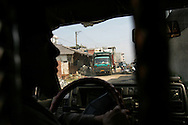 Workers unload electronic waste from trucks as seen from a hidden position inside of a vehicle, in an area where much of the world's electronic waste _ from cell phone chargers to mainframe computers _ ends up in Guiyu and other small towns like it in eastern China, Thursday March 16, 2006. Workers, many of them poorly paid migrants strip, smash and melt down circuit boards, mainly to extract the copper and other precious metals inside. The business has created massive pollution from leaded glass and other toxic materials. A water sample taken from the site revealed lead levels 2,400 times higher than the World Health Organization's limit for drinking water.