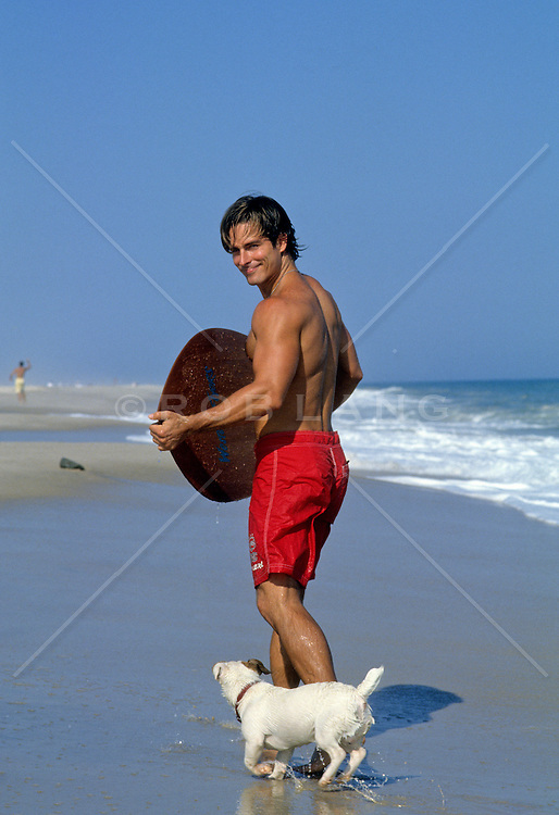 man on the beach with a skim board and dog